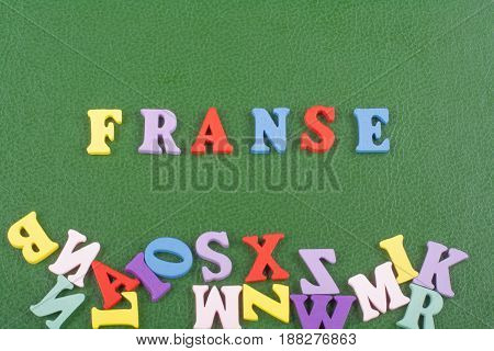 FRENCH word on green background composed from colorful abc alphabet block wooden letters, copy space for ad text. Learning english concept