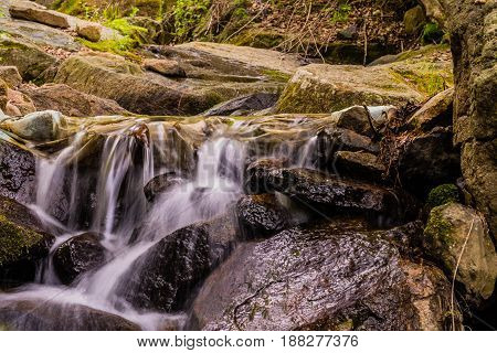 Closeup of a small water fall cascading over large rocks and boulders.