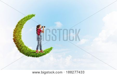 Cute kid girl on green moon and looking in binoculars