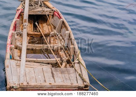 Small wooden rowboat with floating in calm water with ropes leading to the shore