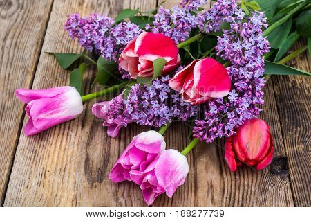 Bouquet of tulips with lilac on wooden background. Studio Photo