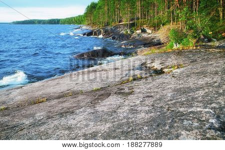 Rocky coast of Onega Lake with prehistoric petroglyphs and evergreen forest - Republic of Karelia Russia. Selective focus.