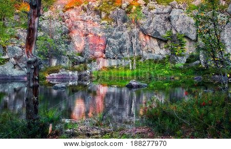 Small beautiful lake under the cliff on Mountain Vottovaara at sunset - summer 2015 Republic of Karelia Russia. Selective soft focus.