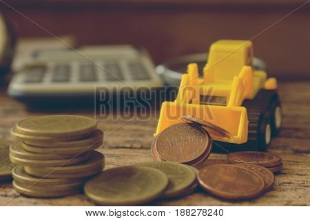concept idea for save money and growth business image of struck or bulldozer toy and coins