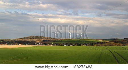 Wind energy business. Wind turbine closeup with blue sky green grass and village