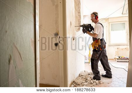 Senior Worker Using Drill At Contruction Site