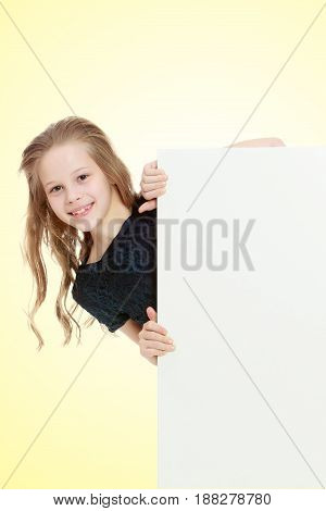Beautiful little girl with her long hair peeks out from behind the banner.On a yellow gradient background.