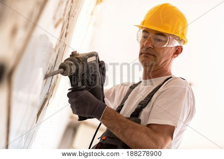 Senior Man Using Drill In The Reconstruction Of The Building