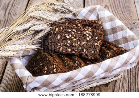 Black rye bread with cereal seeds on white background. Studio Photo