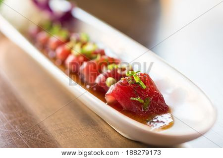 Plate of tuna sashimi. Tuna sashimi is a japanese cuisine dish of thinly sliced fish in japan it is often served as appetizer in restaurants. It can also be made with other raw meat such as salmon.