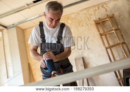 Workerr Repairs The Door In A Carpenter's Workshop