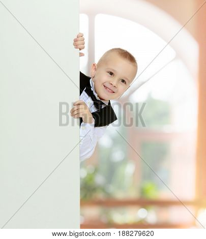 Cute little blonde boy in a black waistcoat and a white shirt and a bow at the neck , peeping over white banner.In a room with a large semi-circular window.