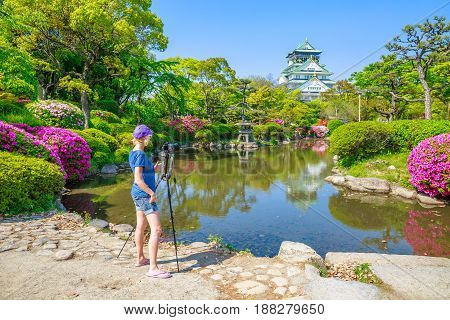 Travel woman photographer with professional camera on tripod takes shot of famous landmark of Osaka Castle in springtime. Freedom and asia travel concept. Osaka, japan