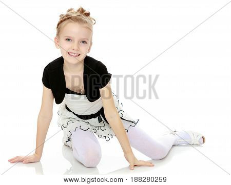 Beautiful little blonde girl dressed in a white short dress with black sleeves and a black belt.Girl sitting on the floor leaning on hands and smiling at the camera.Isolated on white background.