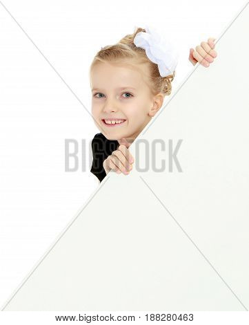 Beautiful little blonde girl dressed in a white short dress with black sleeves and a black belt.The girl peeks out from behind white banner.Close-up.Isolated on white background.