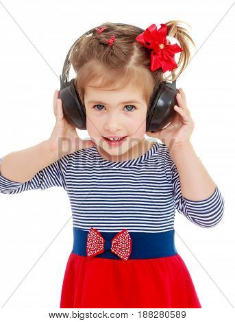 Nice little blonde girl with a red bow on her head, to listen to music through big black headphones. Close-up.Isolated on a white background.