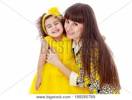 Slender young mother in a short elegant dress and her cute little daughter , embracing, surrounded by Christmas gifts.Isolated on white background.