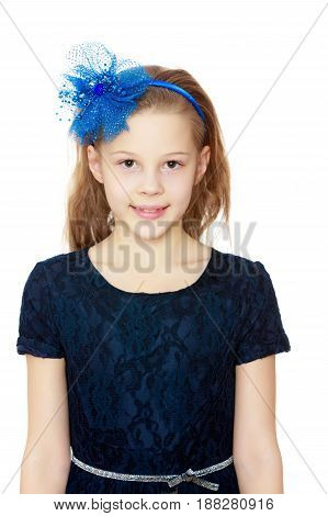 Cute Caucasian little girl In a dark blue dress and big blue bow on her head.Isolated on white background.