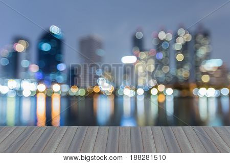 Opening wooden floor Twilight blurred bokeh light city office building with reflection night view abstract background