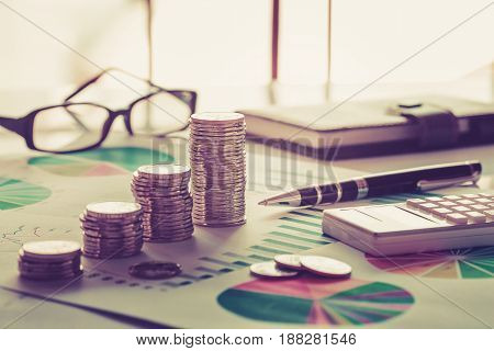 Financial analysis concept with coins, graph, calculator and glasses
