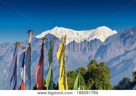 Mount South Kabru (left) and North Kabru (right) snowy peaks 7378 mtrs 24215 feet high one of the highest peaks of Himalayan Mountain range - with top of Rinchenpong Monastery flags in foreground. Rinchenpong Sikkim India