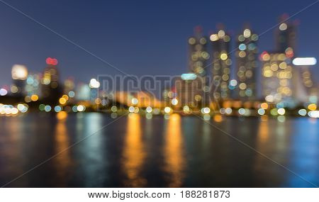 Twilight night blurred bokeh light office building with water reflection abstract background