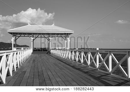 Black and White over wooden pavilion and walkway leading to ocean skyline background