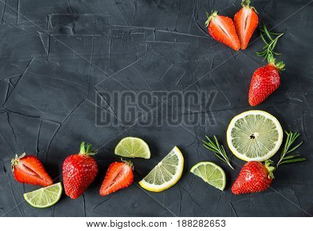Fresh strawberries, lime slices and rosemary on concrete background. top view. space fot text