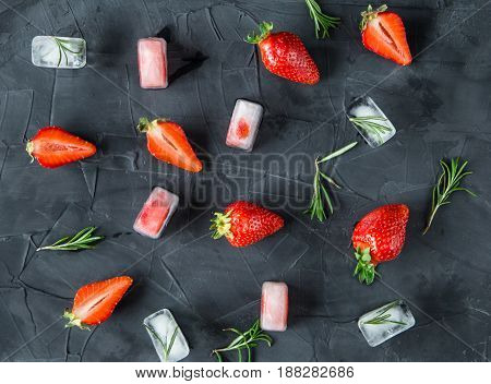 background with fresh strawberry and rosemary and ice cubes with strawberries and rosemary. on concrete background. top view.