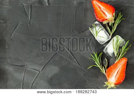 background with fresh strawberry and rosemary and ice cubes with strawberries and rosemary. on concrete background. top view. space foe text