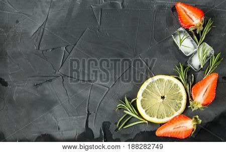 background with fresh strawberry, lemon and rosemary and ice cubes with strawberries and rosemary. on concrete background. top view. space foe text