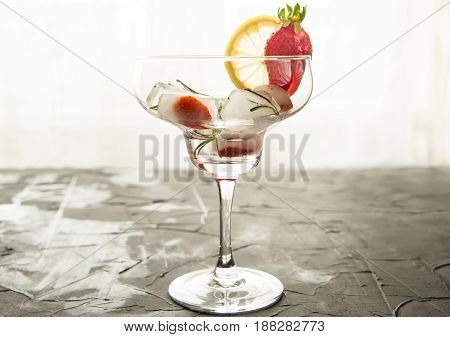cocktail made from Strawberries and rosemary ice cubes into the glass. on concrete background