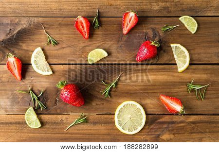 Fresh strawberries, lime slices and rosemary on old wooden background. top view
