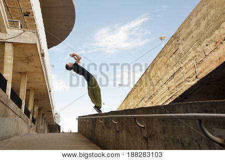 Young man doing a back flip. Parkour in the urban space. Sports in the city. Sport activity.
