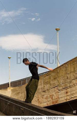 A young man is jumping from a high wall. Parkour in the urban space. Sport in the city. Sport Activities outdoors. Acrobatics