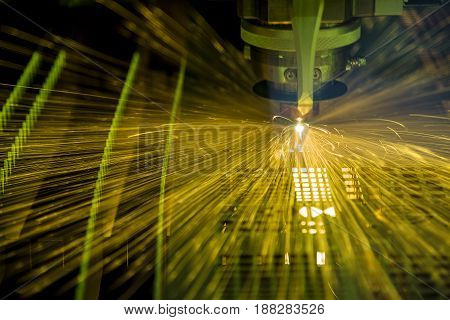 abstract scene of sparking light from fiber laser cutting machine.small dept of field flame light from laser cutting.