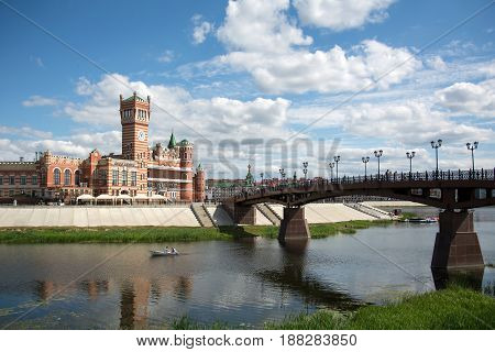 Yoshkar-Ola, Russia - August 10, 2016 Castle on the background of the sunset sky in the water reflection. The complex in which the clock tower. Palace on the embankment.