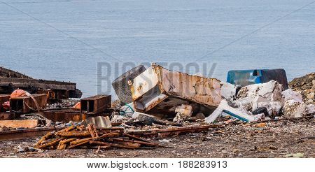 Rusted metal and old refrigerator along with other trash and debris laying on the ground with the ocean in the background in an abandoned shipyard