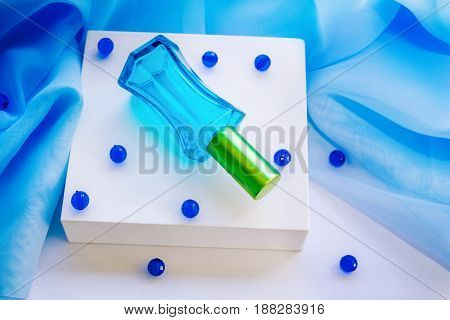 Blue glass perfume bottle on a white box with beads and textile