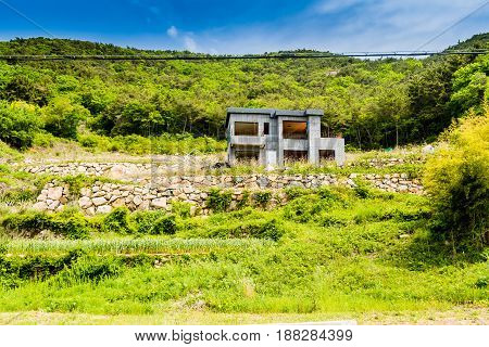 Unfinished abandoned gray concrete house in the side of a hill with stone wall in the foreground and blue sky in the background.