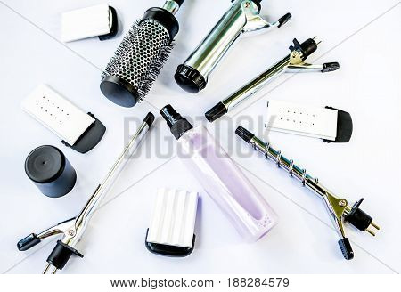 Hairstyling set. Hair curler iron accessories and  thermal protective fluid in a plastic spray bottle on a white background