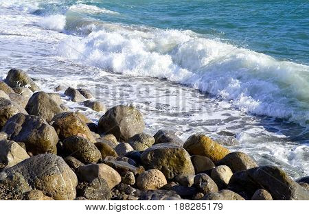 Small sea waves beat on the shore and stones