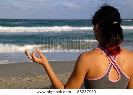 Woman practicing yoga (Lotus Position) on the beach
