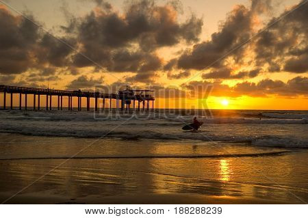Surfer calling it a day near the pier in La Jolla California with a gorgeous sunset in the background