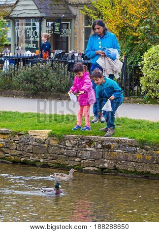 Bourton On The Water England - 7 April 2017 - An Indian boy and girl with their parent enjoy feeding ducks at a river in Bourton On The Water England on April 7 2017