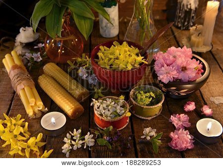 Still life with candles, healing herbs and flowers. Alternative medicine vintage concept
