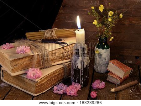 Still life with old book, burning candle and flowers. Alternative medicine vintage concept
