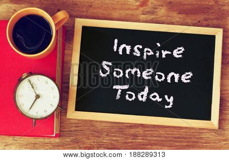 black board with the phrase inspire someone today written on it. over wooden table with coffee and vintage clock