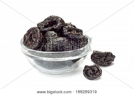 Bowl of dried plums isolated on white background
