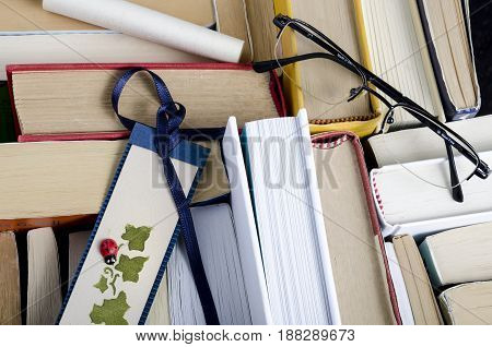 top view of a group of books bookmark and a pair of glass. culture. education.